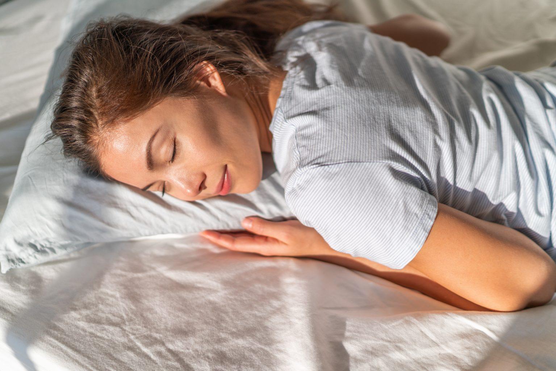 bed asian girl sleeping on stomach sleeper resting head on foam pillow.